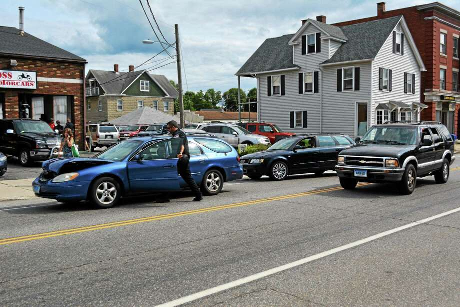 Jenny Golfin - Register Citizen. Torrington Police Officer Robert Simon moves one of the vehicles involved in a three-car accident on East Main Street out of the roadway to help clear the way for traffic Tuesday afternoon. The two station wagons, pictured at left, were involved in the accident. Photo: Journal Register Co.