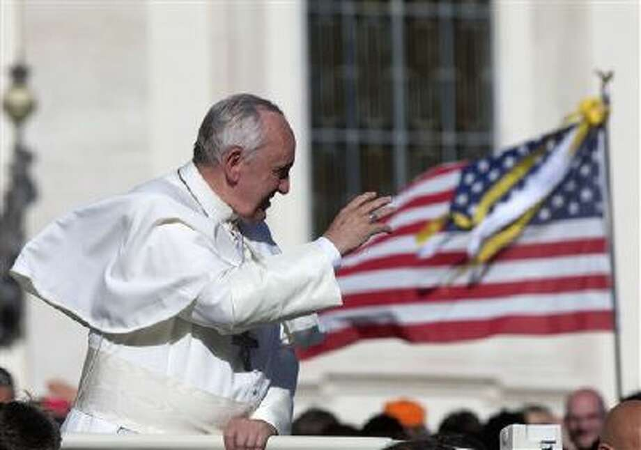 A US flag is seen in the background as Pope Francis is driven away Nov. 6 at the end of his weekly general audience in St. Peter's Square at the Vatican. Photo: AP / AP