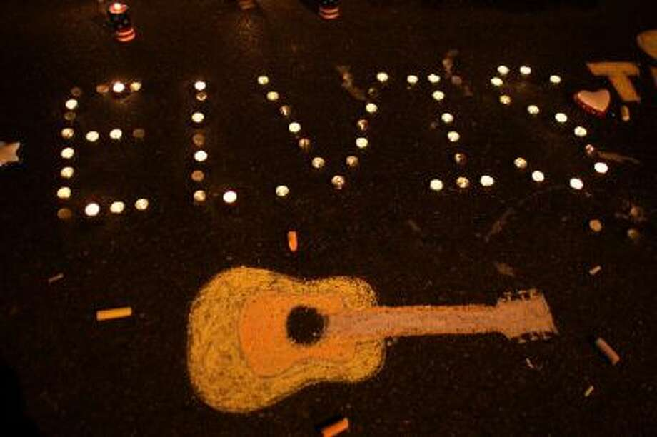 """Candles spell out """"Elvis"""" beside a chalk drawing of a guitar on the ground during a vigil held by fans in memory of the late singer outside the front gates of Graceland Mansion, the home of Elvis Presley, on August 15, 2007 in Memphis, Tennessee. Photo: Getty Images / 2007 Getty Images"""