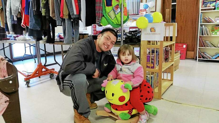 Clinton Perrett of Torrington and 20-month-year-old McKenna Hopkins enjoyed browsing the Tots Treasures Kids Consignment Sale at United Congregation Church in Torrington Saturday. Photo: N.F. Ambery — Special To Register Citizen