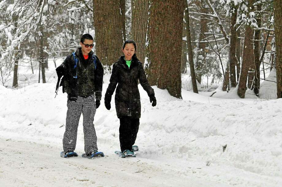 Jon Choi of New Haven and Lilai Guo of New York City snowshoe on their first trip through White Memorial in Litchfield. Photo: Laurie Gaboardi—Register Citizen