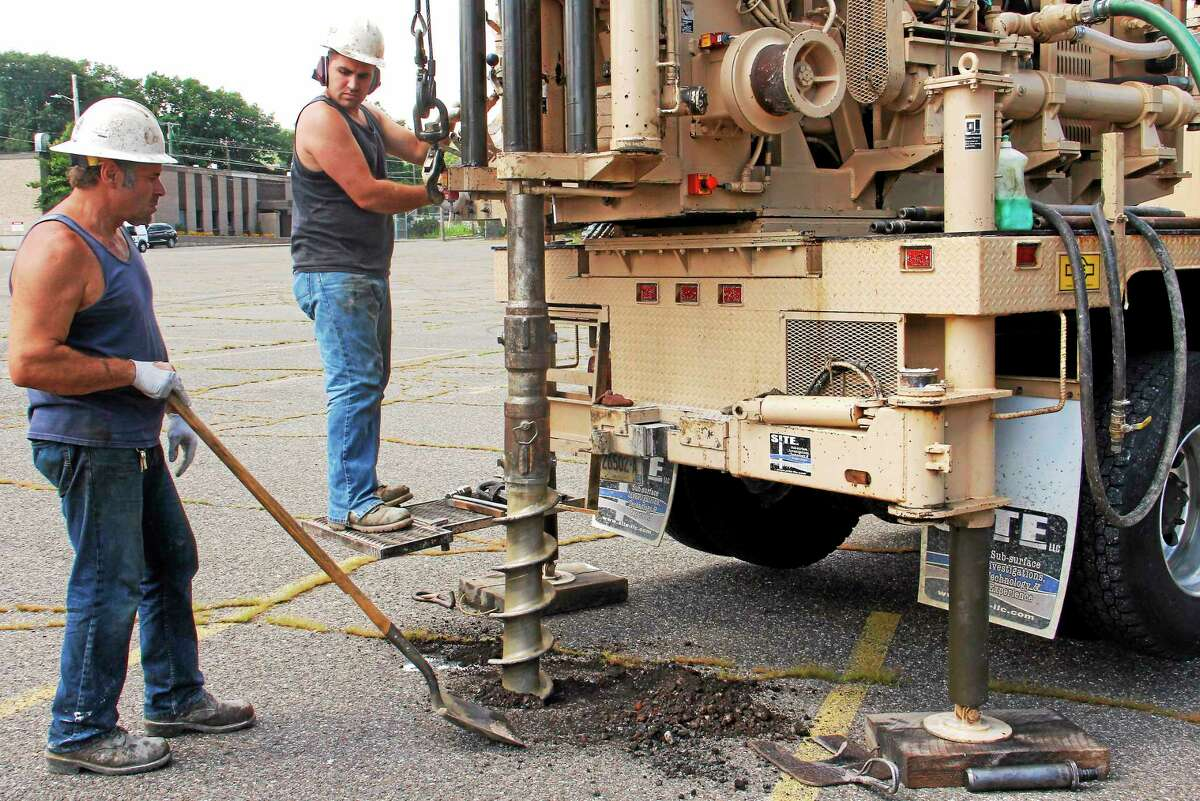 From left: John DeAngelis Jr. and his son, John DeAngelis III, work on drilling a hole with a hollow-stem auger on the Field Street parking lot Monday in Torrington. The drilling is being completed for soil sampling of the site of the upcoming Litchfield County Courthouse complex.