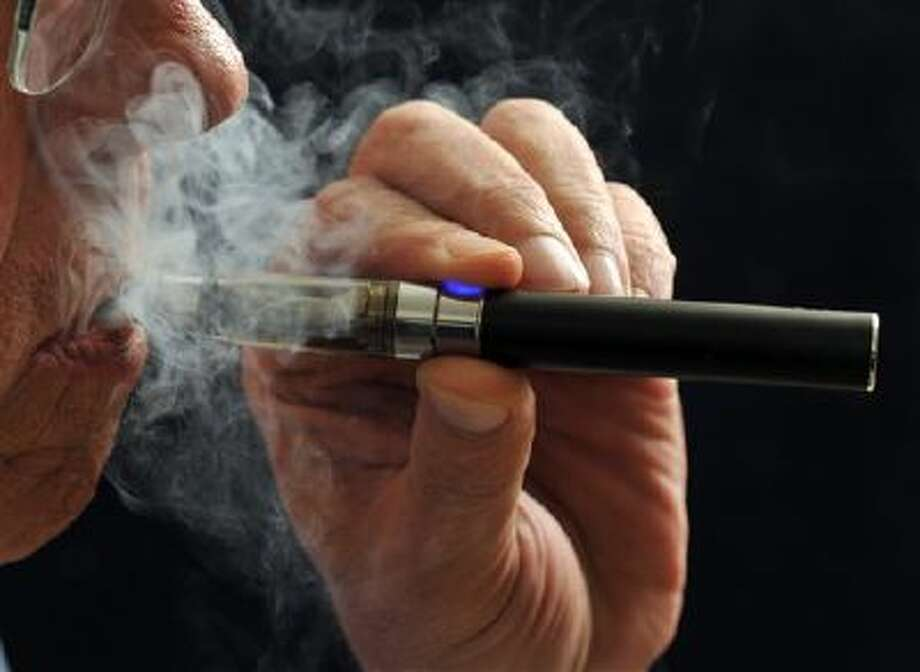 In this photo illustration, a smoker puffs on an e-cigarette. E-cigarettes are being touted as a safe alternative to traditional lighted tobacco products. Studies are looking at the chemical makeup of the secondhand vapor, which is breathed out like smoke. Photo: AP / Wichita Falls Times Record News