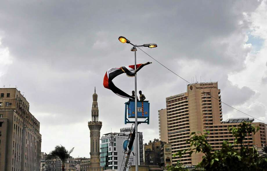 Egyptian laborers hang a national flag on a street light two days before the commemoration of deadly clashes with security forces in 2011, in Tahrir Square, Cairo, Egypt, Sunday, Nov. 17, 2013. Egyptian authorities are building a memorial in Cairo's Tahrir Square dedicated to protesters killed in the country's turmoil, only days before a highly charged second anniversary marks one of the fiercest confrontations between demonstrators and security forces in the area that left scores dead. (AP Photo/Nariman El-Mofty) Photo: AP / AP
