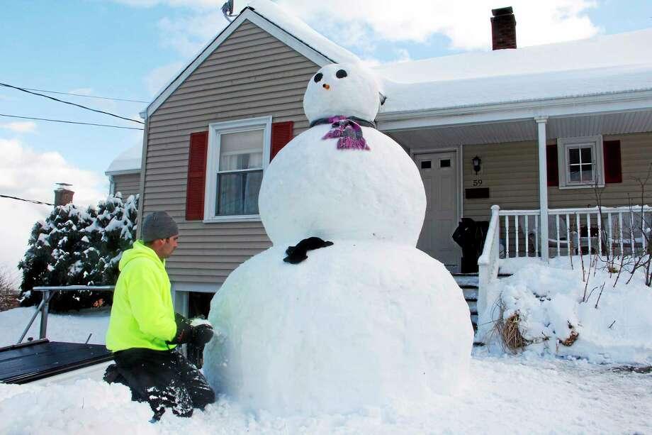 Brandon Blatchley builds an 8-foot-tall snowman on his lawn on Eggleston St in Torrington on Friday. Photo: Esteban L. Hernandez - The Register Citizen
