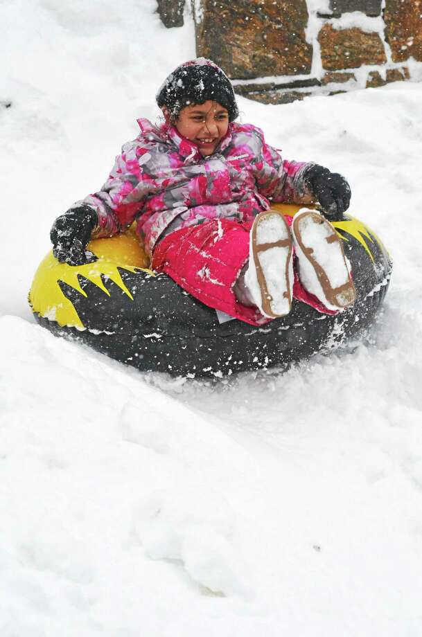 Genesis Colabro, 8, of Torrington, gets some early sledding in while the snow was still coming down Thursday afternoon. Photo: John Berry—The Register Citizen