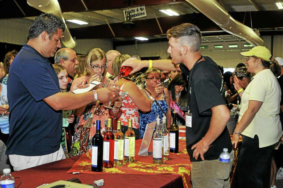 Dozens of people line up at one of the many tasting stations at the Connecticut Wine Festival at the Goshen Fairgrounds Saturday. Photo: Laurie Gaboardi — The Register Citizen