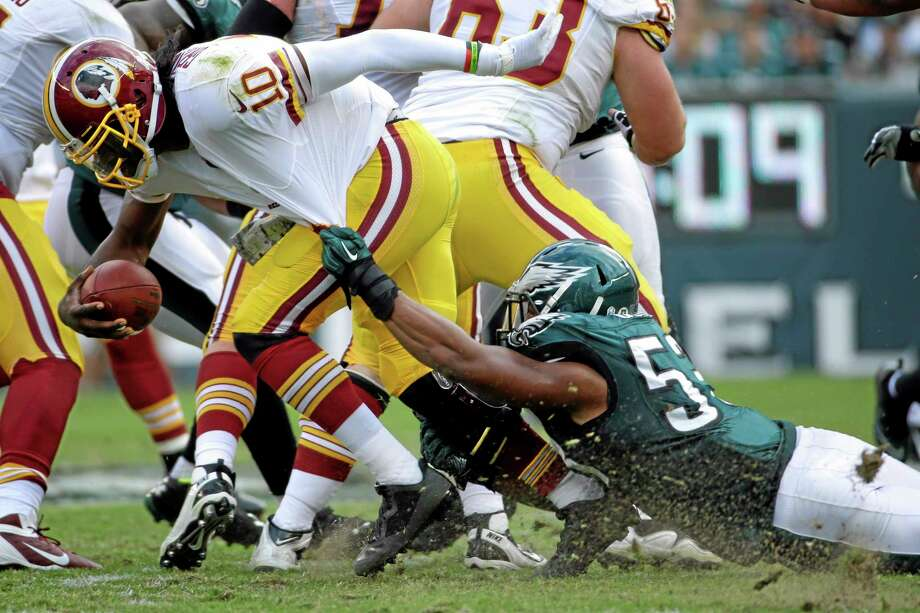 Washington Redskins quarterback Robert Griffin III (10) is dragged to the turf by Philadelphia Eagles linebacker Najee Goode during the first half of an NFL football game in Philadelphia, Sunday, Nov. 17, 2013. (AP Photo/Matt Slocum) Photo: AP / AP