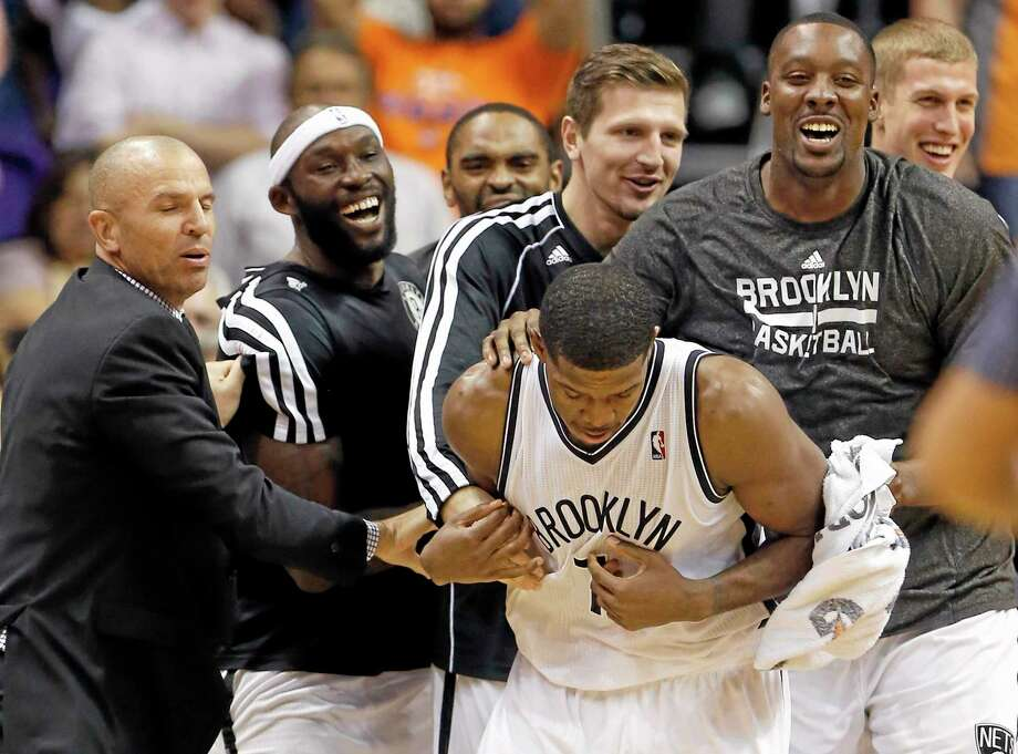 The Brooklyn Nets' Joe Johnson is surrounded by teammates after making the game-winning shot in overtime against the Suns on Friday night in Phoenix. Photo: Matt York — The Associated Press  / AP
