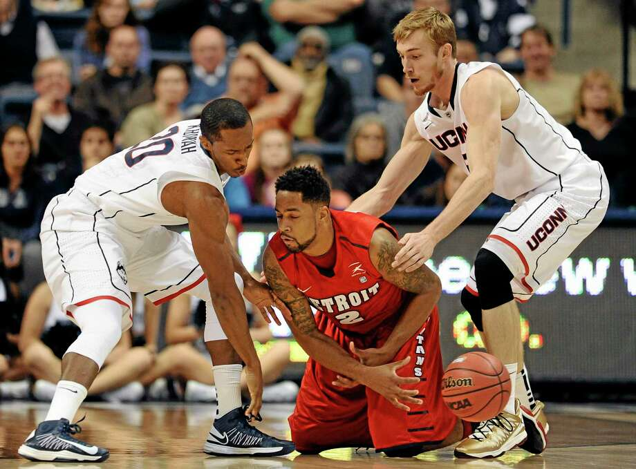 UConn's Lasan Kromah, left, Niels Giffey and the rest of the Huskies will have opponents on their knees this season, just like Detroit's Juwan Howard Jr. was on Thursday night, according to Register sports columnist Chip Malafronte. Photo: Jessica Hill — The Associated Press  / FR125654 AP