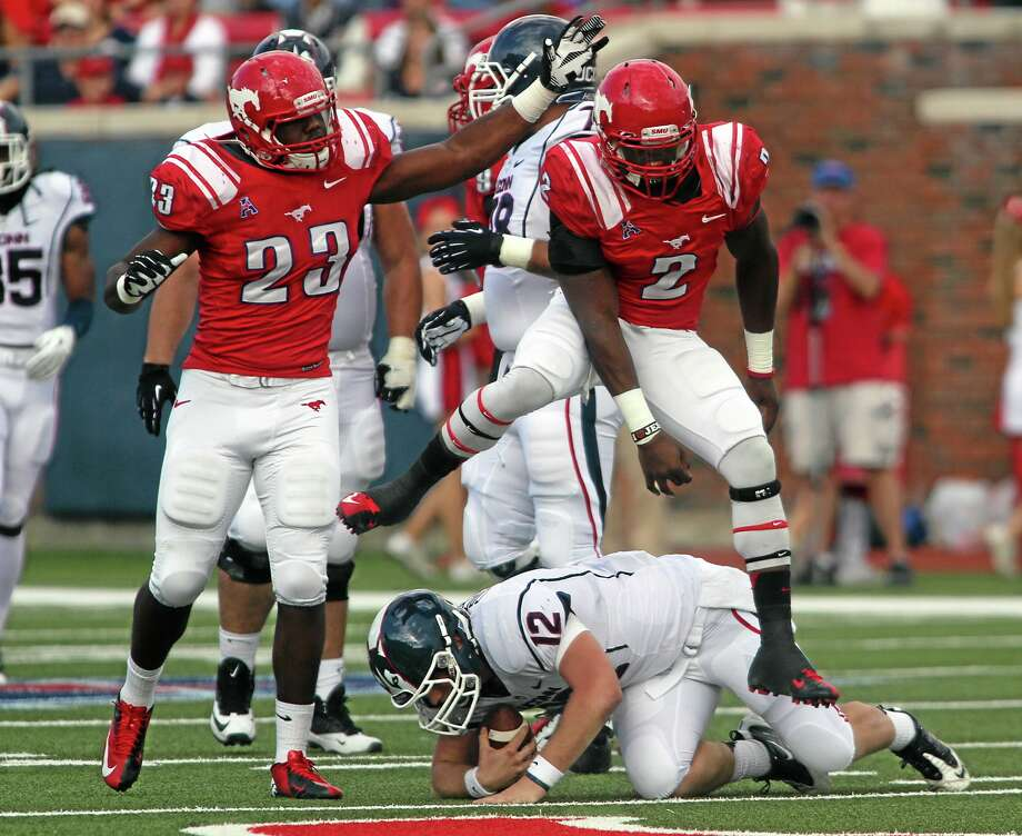 Ricky Moon/The Dallas Morning News/AP Photo SMU's Stephon Sanders (23) and Jonathan Yenga (2) celebrate after sacking UConn's Casey Cochran (12) in the first half on Saturday. Photo: AP / The Dallas Morning News
