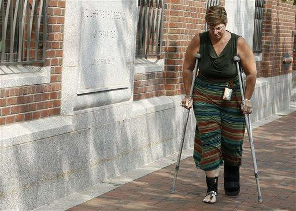 Boston Marathon bombing victim Karen Brassard leaves federal courthouse following the arraignment of bombing suspect Dzhokhar Tsarnaev Wednesday, July 10, 2013, in Boston. The April 15 attack killed three and wounded more than 260. The 19-year-old Tsarnaev has been charged with using a weapon of mass destruction, and could face the death penalty. (AP Photo/Winslow Townson)