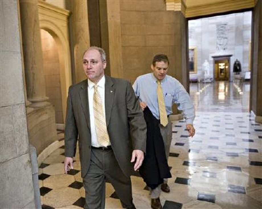 Rep. Steve Scalise, R-La., left, and Rep. Jim Jordan, R-Ohio, leave the office of House Speaker John Boehner, R-Ohio on Friday before a vote on Obamacare. Photo: AP / AP