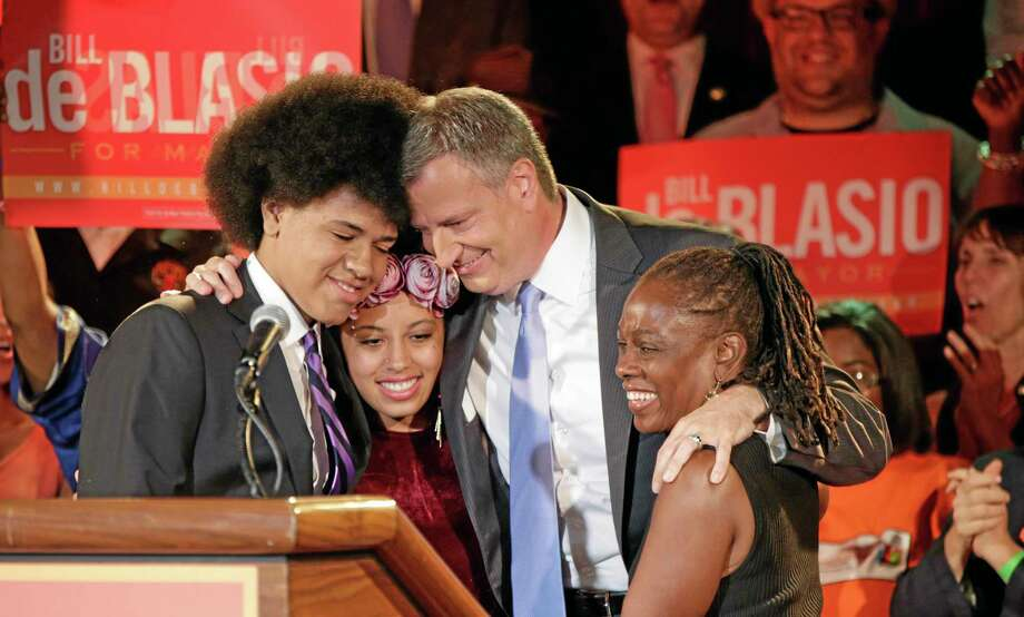 FILE - In this Tuesday, Sept. 10, 2013 file photo, New York Democratic mayoral candidate Bill de Blasio embraces his son Dante, left, daughter Chiara, second left, and wife Chirlane McCray after polls closed in the city's primary election in New York. De Blasio and his wife settled in the Park Slope neighborhood of the Brooklyn borough of New York largely because they felt that their interracial relationship would be accepted there, the mayor-elect has said. (AP Photo/Kathy Willens, File) Photo: AP / AP