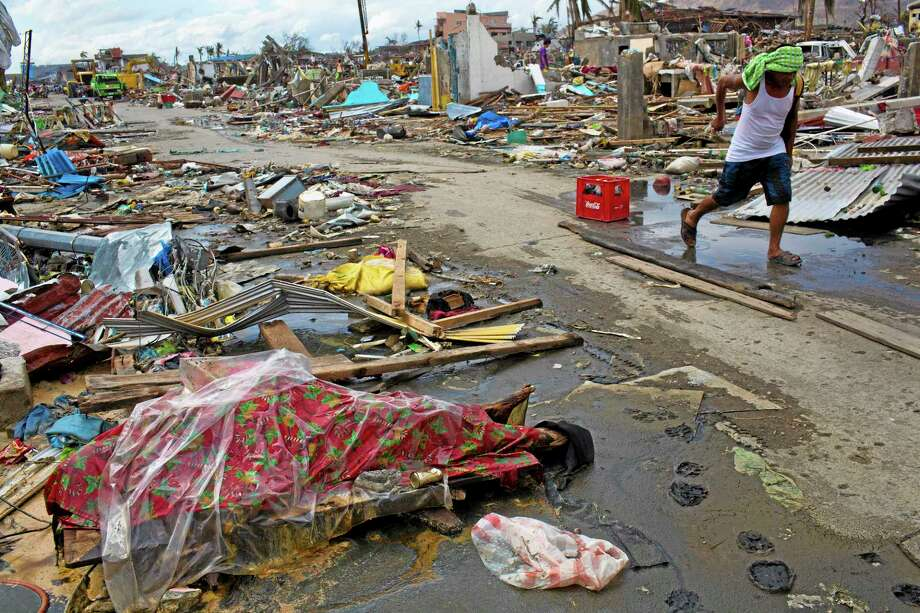 A Typhoon Haiyan survivor walks past a dead body, wrapped in plastic Christmas theme wrapping in Tacloban on Saturday Nov. 16, 2013.  One week after Typhoon Haiyan  razed the eastern part of the Philippines, leaving 600,000 homeless, survivors have begun rebuilding, with or without help from their government or foreign aid groups.  (AP Photo/David Guttenfelder) Photo: AP / AP