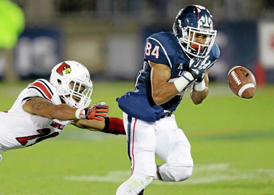 UConn receiver Brian Lemelle drops a pass as he is pressured by Louisville safety Hakeem Smith during the second half of the Huskies' 31-10 loss on Nov. 8 in East Hartford. Photo: Charles Krupa — The Associated Press  / AP