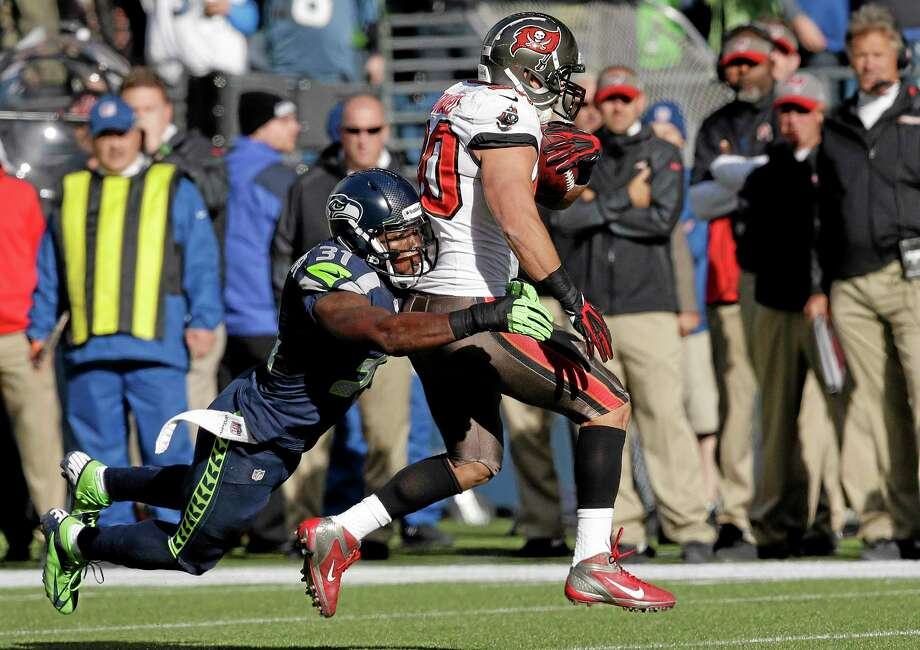 Tampa Bay Buccaneers running back Brian Leonard gets tackled by Seahawks strong safety Kam Chancellor during the first half of a Nov. 3 game in Seattle. The Register's Dan Nowak feels Leonard is a prime pickup if you need a running back. Photo: Elaine Thompson — The Associated Press  / AP