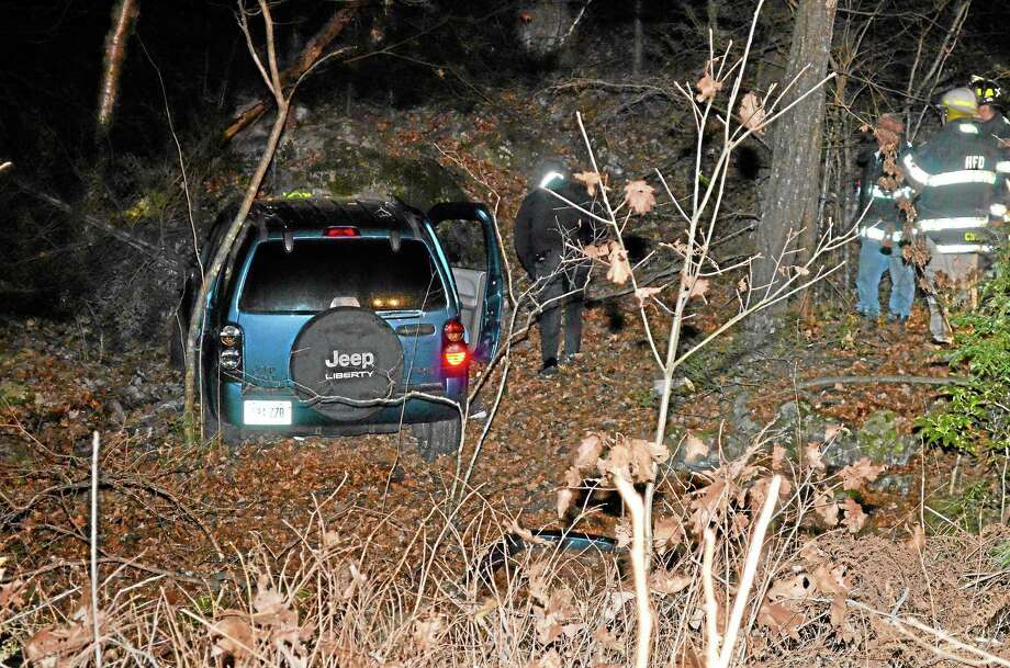A blue Jeep Liberty traveled into the woods after veering off of Plymouth Road in Harwinton on Thursday night. Photo: Kate Hartman — Register CitizeN
