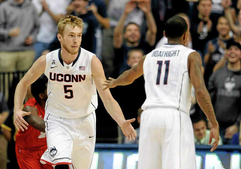 UConn's Niels Giffey, left, and Ryan Boatright celebrate a basket by Giffey during the first half of Thursday's win over Detroit. Photo: Jessica Hill — The Associated Press  / FR125654 AP