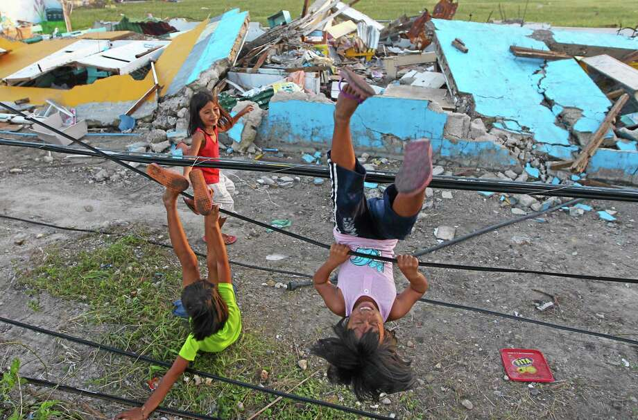 Young survivors of Typhoon Haiyan play with fallen power lines near a damaged school in Guiuan, Philippines, Thursday, Nov. 14. Typhoon Haiyan, one of the most powerful storms on record, hit the country's eastern seaboard on Friday, destroying tens of thousands of buildings and displacing at least a half-million people.  (AP Photo/Dita Alangkara) Photo: AP / AP