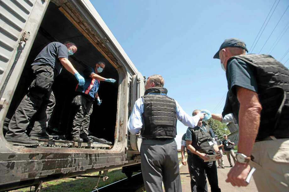 Deputy head of the OSCE mission to Ukraine Alexander Hug, center back to the camera, speaks to a member of Netherlands' National Forensic Investigations Team on the platform as a refrigerated train loaded with bodies of the passengers departs the station in Torez, eastern Ukraine, 15 kilometers (9 miles) from the crash site of Malaysia Airlines Flight 17, Monday, July 21, 2014. (AP Photo/Evgeniy Maloletka) Photo: AP / AP