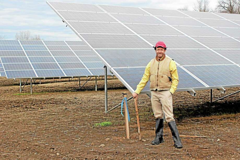 Ben Freund, co-owner of Freund's Farm in East Canaan, with the farm's new array of solar panels. Photo: Shako Liu—Register Citizen