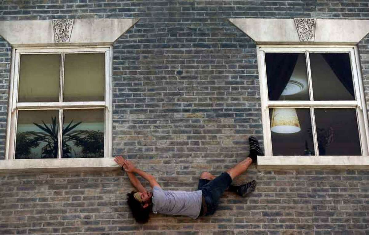 A visitor enjoys an art installation by Argentine artist Leandro Erlich in east London, Tuesday, July 9, 2013. Internationally known for his three-dimensional visual illusions, Erlich has been commissioned to create a new installation in Dalston area of the capital. Resembling a theatre set, the detailed facade of a Victorian terraced house, recalling those that once stood on the street, lies horizontally on the ground with mirrors positioned overhead. The reflections of visitors give the impression they are standing on, suspended from, or scaling the building. (AP Photo/Lefteris Pitarakis)