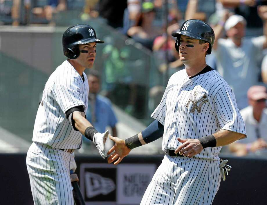 The Yankees' Kelly Johnson, right, celebrates with Jacoby Ellsbury after scoring during the fifth inning against the Reds on Sunday. Photo: Seth Wenig — The Associated Press   / AP