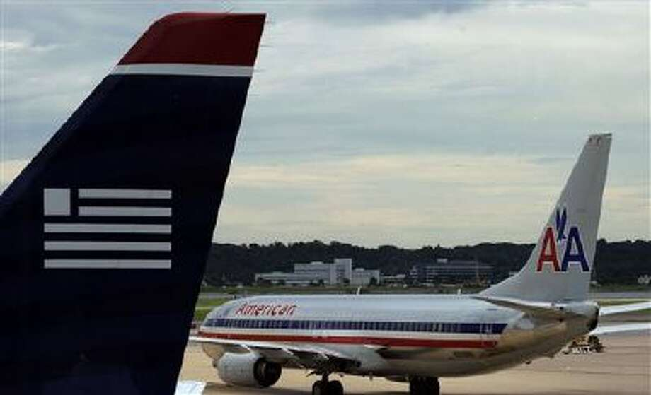 An American Airlines plane and a US Airways plane are parked at Washington's Ronald Reagan National Airport. Photo: AP / AP