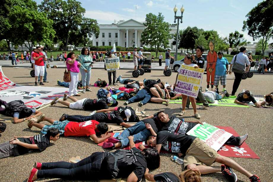 This July 24, 2013, file photo shows demonstrators lying in front of the White House in Washington to represent deported family members during a rally for immigration reform. The sudden rise in the number of families and unaccompanied minors from Central America crossing the border in two United States has refocused attention on immigration, but hardly under the terms that President Barack Obama and immigrant advocates had once envisioned. Now the White House says it's focused on stanching the influx of border crossers and returning as many as quickly as the government can. Photo: AP Photo  / AP