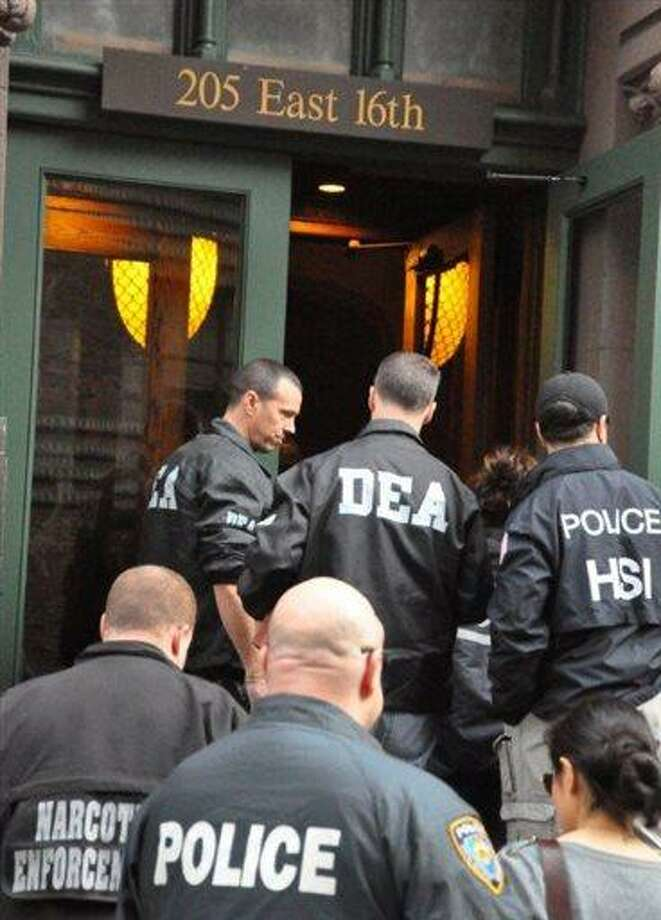In this March 26, 2013 photo provided by the Office of the Special Narcotics Prosecutor for the City of New York, officers from the New York City Police Department and the U.S. Drug Enforcement Administration raid the New York City office of Dr. Hector Castro. Authorities say that Castro led a narcotics smuggling ring that trafficked at least $10 million worth of drugs across several states. (AP Photo/Office of the Special Narcotics Prosecutor for the City of New York) Photo: AP / NYC Office of the Special Narcotics Prosecutor