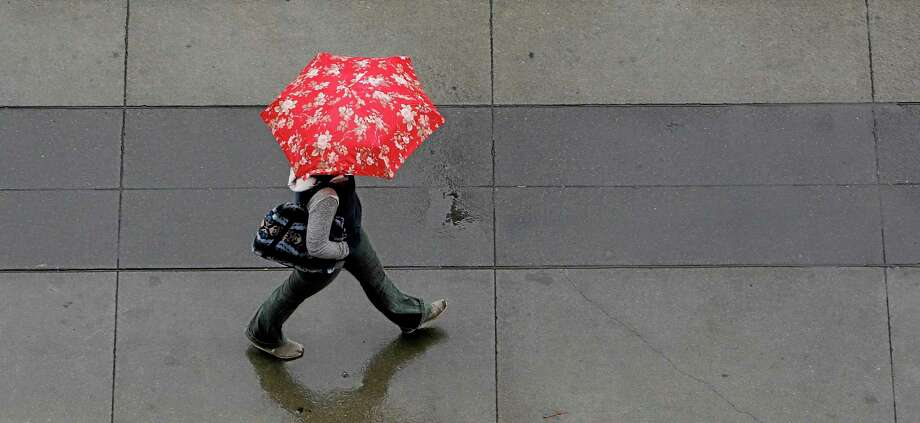 Umbrellas were put to good use as showers swept through Sacramento, Calif., Friday, Feb. 7, 2014. Drought-stricken California is getting some relief as a storm system the likes of which, forecasters say, the region has not seen in more than a year.(AP Photo/Rich Pedroncelli) Photo: AP / AP
