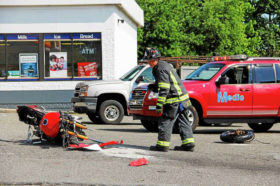 A Torrington Police firefighter stands near a wrecked motorcycle near the intersection of East Main Street and Pineridge Road after a collision on Sunday in Torrington. Photo: Esteban L. Hernandez — Register Citizen