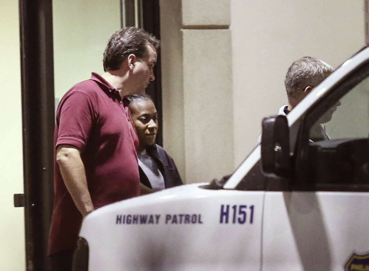Carlesha Freeland-Gaither, second from left, is escorted from Howard County General Hospital in Columbia, Md. early Thursday morning, Nov. 6, 2014, by Philadelphia Detectives James Sloan, left, and John Geliebter, right, partially obscured. Freeland-Gaither was abducted off the streets of Philadelphia Sunday night night. Law enforcement agents rescued her Wednesday outside Baltimore and arrested suspect Delvin Barnes.