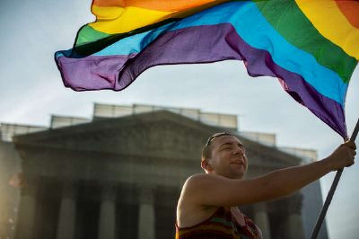 A gay-rights supporter waves a flag in front of the Supreme Court in June when the court knocked down a federal bill banning rights for same-sex married couples. But not everything has been rosy for the movement.