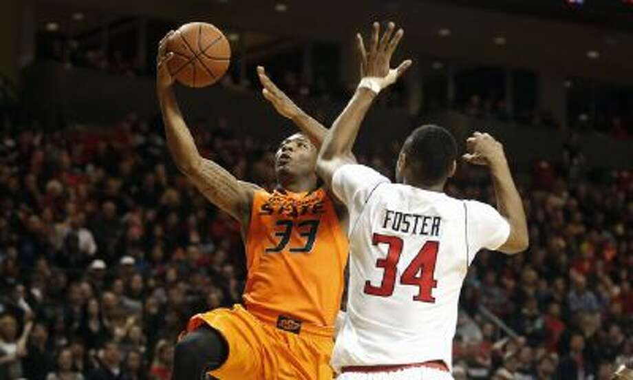 Oklahoma State's Marcus Smart (33) looks to score past Texas Tech's Alex Foster (34) during their NCAA college basketball game in Lubbock, Texas, Saturday.