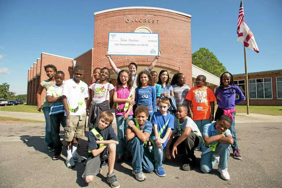 "Fifth grade teacher John Herber of Oakcrest Elementary School and students gather in front of the school after receiving the PEOPLE 2013 ""Teacher of the Year"" Award, on Monday, Oct. 28, 2013 in Pensacola, Fla. Photo: Michael Spooneybarger—Invision For PEOPLE Magazine—AP Images  / Invision"