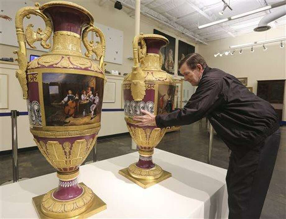 In this photo, Jerry Holley, executive vice president of Dallas Auction Gallery, rotates a rare Russian vases made in 1833 by Russia's Imperial Porcelain Factory and on display at the gallery in Dallas. The rare 4 1/2-foot tall vases, which had been packs away for around a decade, were sold Thursday for $2.7 million in a private sale about a week before they were to be auctioned. (AP Photo/LM Otero) Photo: AP / AP