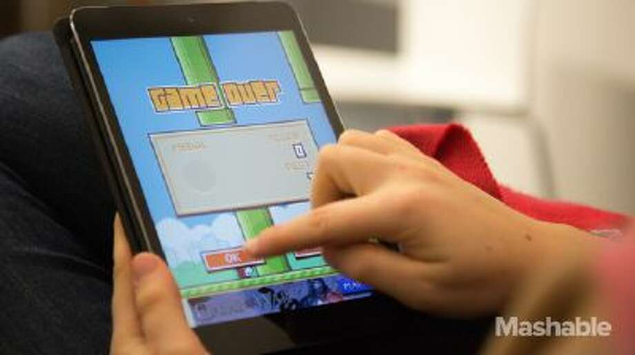 "A person plays a game of ""Flappy Bird"" on an iPad."