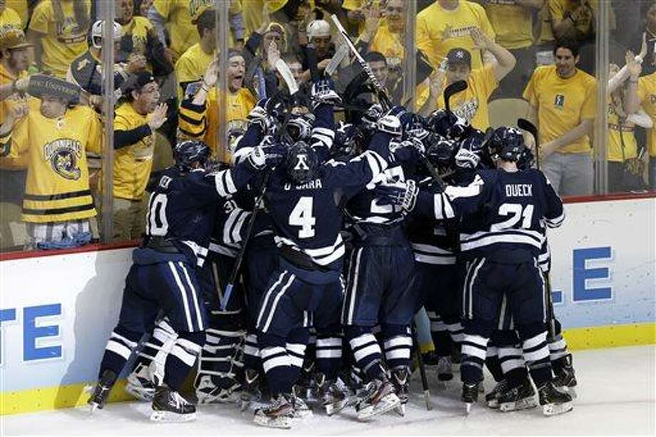 The Yale bench piles on right wing Andrew Miller to celebrate his game-winning overtime goal against UMass Lowell during an NCAA Frozen Four college hockey semifinal in Pittsburgh on Thursday, April 11, 2013. Yale won 3-2. (AP Photo/Gene J. Puskar) Photo: ASSOCIATED PRESS / AP2013
