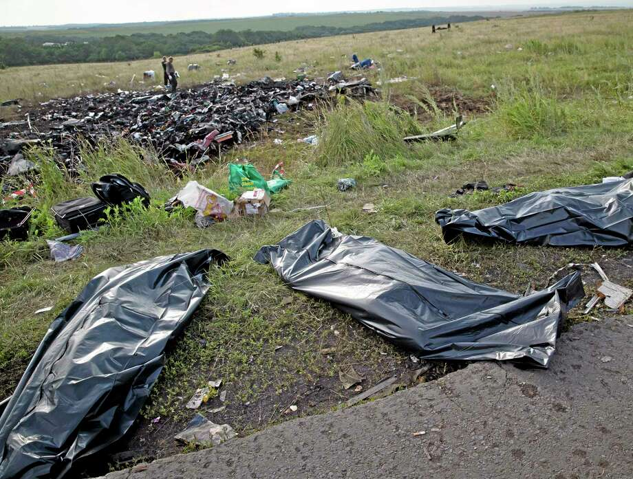 Bodies of victims are covered in plastic sacks at the crash site of Malaysia Airlines Flight 17 near the village of Hrabove, eastern Ukraine. World leaders demanded Friday that pro-Russia rebels who control the eastern Ukraine crash site of Malaysia Airlines Flight 17 give immediate, unfettered access to independent investigators to determine who shot down the plane. Photo: AP Photo — Vadim Ghirda   / AP