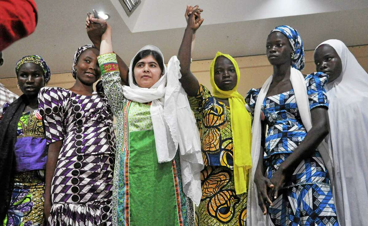 Pakistani activist Malala Yousafzai, centre, raises her hands with some of the escaped kidnapped school girls of government secondary school Chibok during a news confrence, in Abuja, Nigeria, Monday, July 14, 2014. Yousafzai on Monday won a promise from Nigeriaís leader to meet with the parents of some of the 219 schoolgirls held by Islamic extremists for three months. Malala celebrated her 17th birthday on Monday in Nigeria with promises to work for the release of the girls from the Boko Haram movement.