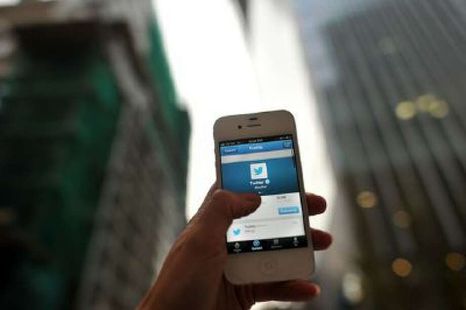 In this photo illustration, The Twitter logo is displayed on a mobile phone. Photo: Getty Images / 2013 Getty Images