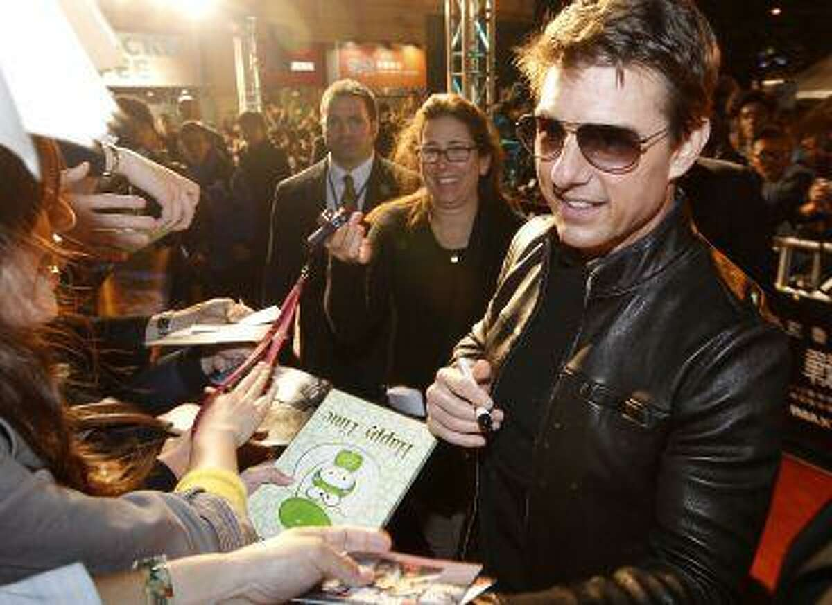 Actor Tom Cruise signs autographs for supporters as he arrives on the red carpet for the premiere of his latest movie