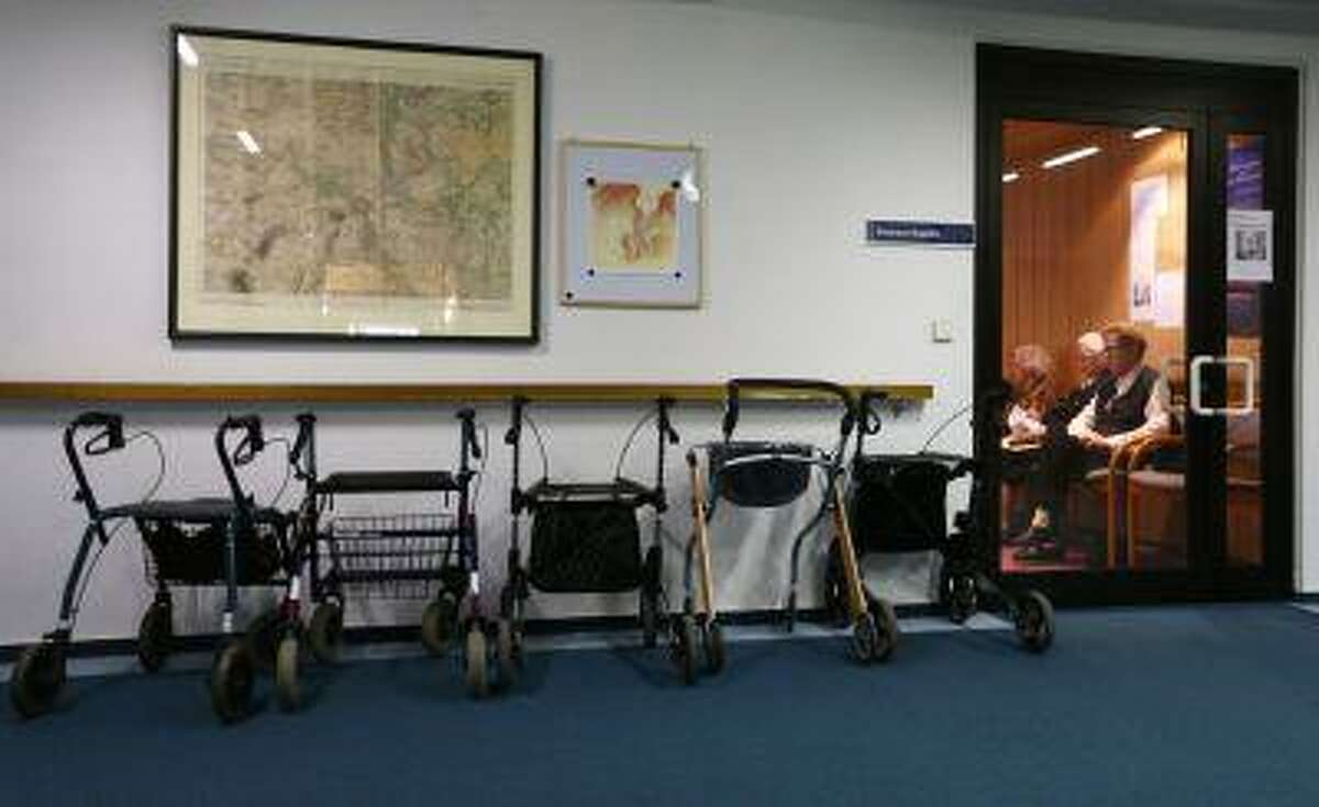 Walking aid chairs are parked outside the residence's chapel as inhabitants attend the church service in a nursing home.