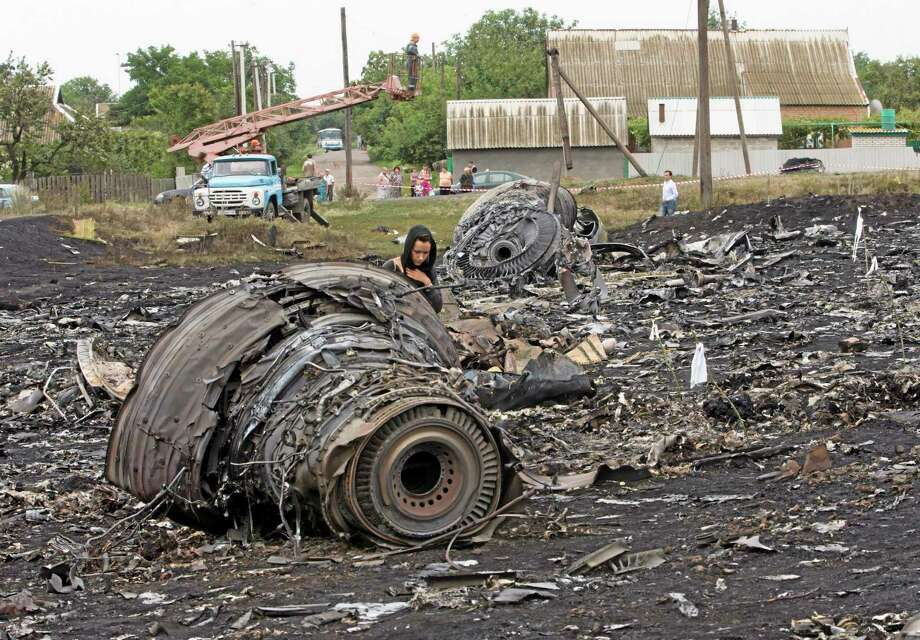 A woman walks at the site of a crashed Malaysia Airlines passenger plane near the village of Rozsypne, eastern Ukraine Friday, July 18, 2014. Rescue workers, policemen and even off-duty coal miners were combing a sprawling area in eastern Ukraine near the Russian border where the Malaysian plane ended up in burning pieces Thursday, killing all 298 aboard. (AP Photo/Dmitry Lovetsky) Photo: AP / AP