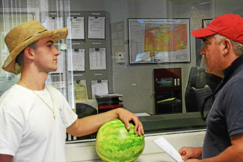 Carmine Cervellino, left, and his son, Ryan, stop at the Thomaston Police Department Friday to drop off a watermelon. Photo: Isaac Avilucea — Register Citizen