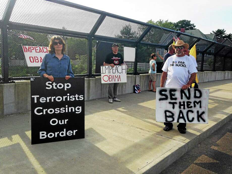(Mercy Quaye - New Haven Register)  A handful of protesters rally on Howard Avenue bridge over I-95 in New Haven Friday. They contend that undocumented migrant children should not be brought to Connecticut Photo: Journal Register Co.