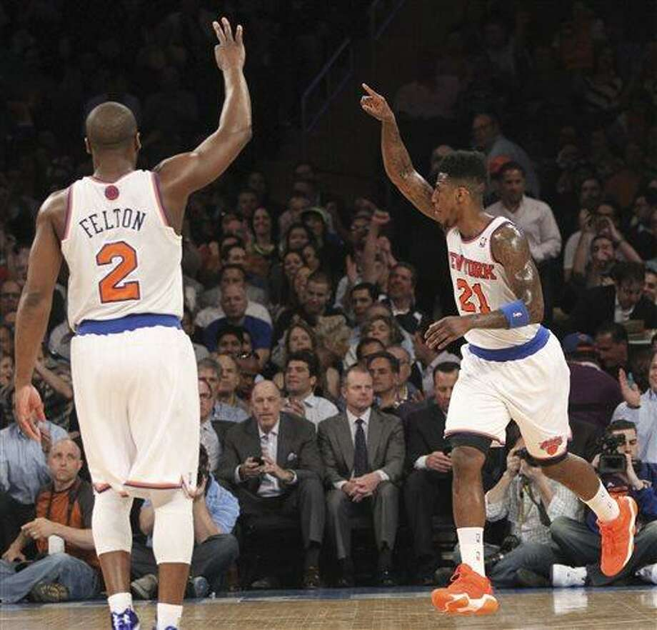 New York Knicks' Iman Shumpert (21) and Raymond Felton gesture after Shumpert made a three-point basket in the first half of an NBA basketball game against the Washington Wizards, Tuesday, April 9, 2013, at Madison Square Garden in New York. The Kincks won 120-99.  (AP Photo/Mary Altaffer) Photo: AP / AP