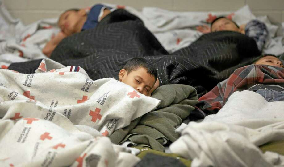 FILE - This June 18, 2014, file photo, detainees sleep in a holding cell at a U.S. Customs and Border Protection,  processing facility in Brownsville,Texas. Immigration courts backlogged by years of staffing shortages and tougher enforcement face an even more daunting challenge since tens of thousands of Central Americans began arriving on the U.S. border fleeing violence back home. For years, children from Central America traveling alone and immigrants who prove they have a credible fear of returning home have been entitled to a hearing before an immigration judge. (AP Photo/Eric Gay, Pool, File) Photo: AP / Pool AP